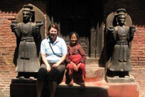 Gast sitzt mit einer Nepalesin vor einem Tempel