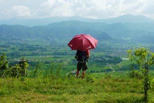 Gast mit Schirm in den grünen Feldern Nepals