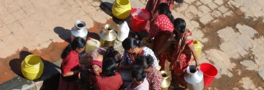 hier sieht man Frauen, sie am öffentlichen Brunnen Wasser holen