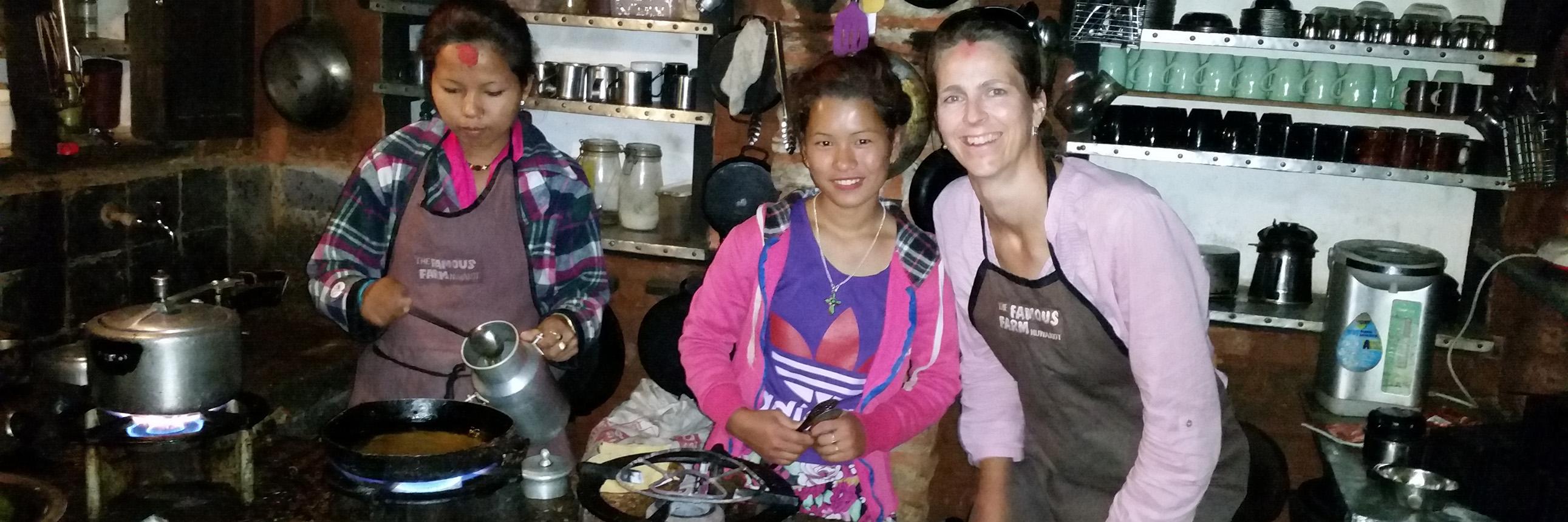 Inhaberin Julia Opitz beim Kochen mit jungen Mädchen in Nuwakot
