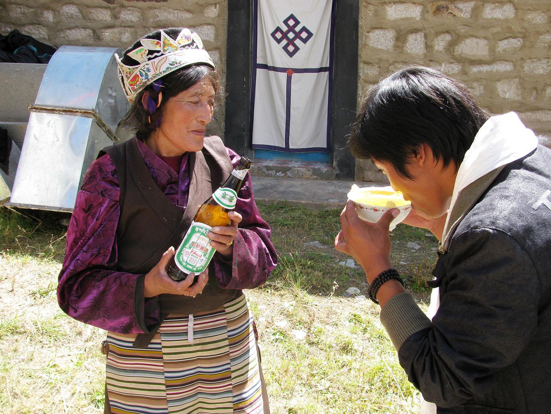 eine Tibeterin begruesst Gaeste mit Lhasa Bier